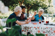 Cheerful senior woman playing cards with males at table in back yard - MASF11526