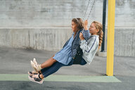Full length of carefree sisters swinging together on swing at playground - MASF11544