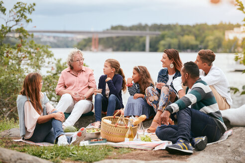 Family and friends looking at senior woman while sitting on lakeshore in park - MASF11556