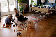 Mother and daughter playing with train set in living room at home - MASF11586