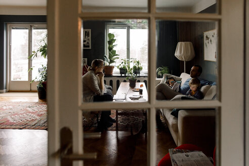Family using various technologies in living room seen through transparent door at home - MASF11589