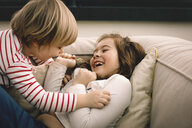 Playful girl tickling cheerful sister on couch at home - MASF11595