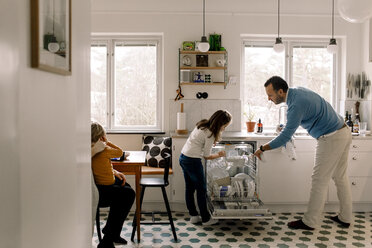 Father and daughter arranging utensils in dishwasher while standing at kitchen - MASF11604