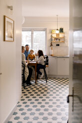 Family having meal together in kitchen seen through corridor at home - MASF11610