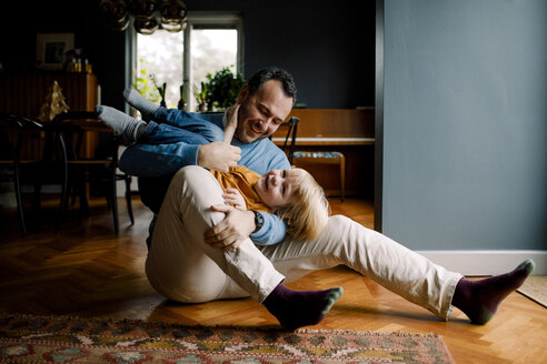 Full length of happy playful father carrying daughter while sitting on hardwood floor at home - MASF11613