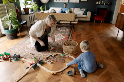 Mother looking at daughter playing with train set in living room - MASF11619