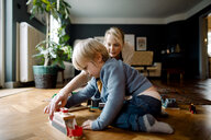 Mother and daughter playing with toy train on hardwood floor in living room at home - MASF11622