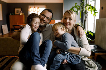 Portrait of parents with cheerful daughters sitting in living room at home - MASF11625