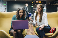 Smiling female multi-ethnic colleagues discussing over laptop and credit card while sitting at airport lobby - MASF11631
