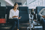 Young businesswoman text messaging through smart phone while sitting with passport in waiting room at airport - MASF11661