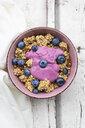 Granola with blueberries and blueberry yoghurt in bowl on white wood - LVF07885
