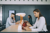 Young businesswoman using smart phone while sitting with multi-ethnic colleagues at table waiting in airport departure a - MASF11676