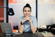 Portrait of confident creative businesswoman sitting at desk in office - MASF11700
