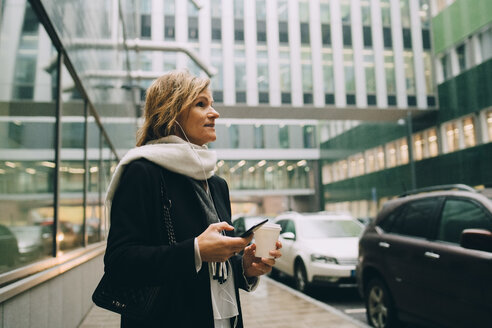 Businesswoman with coffee and smart phone looking away while standing on sidewalk against modern building in city - MASF11748