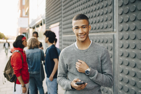 Portrait of smiling teenage boy holding mobile phone while friends standing in background on street - MASF11778
