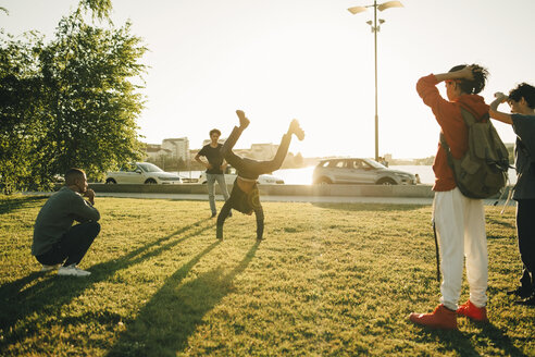 Friends watching teenage boy doing handstand on field during sunny day - MASF11784