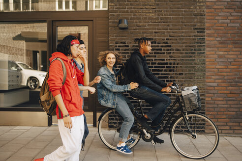 Cheerful young man looking at friends while riding on bicycle in city - MASF11802
