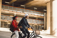 Side view of young man riding bicycle with friend in city - MASF11826