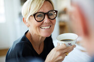 Smiling mature woman holding coffee cup while looking away at home - MASF11829