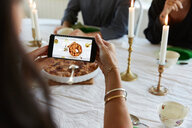 Mature woman using smart phone while having lunch with friends at home - MASF11832