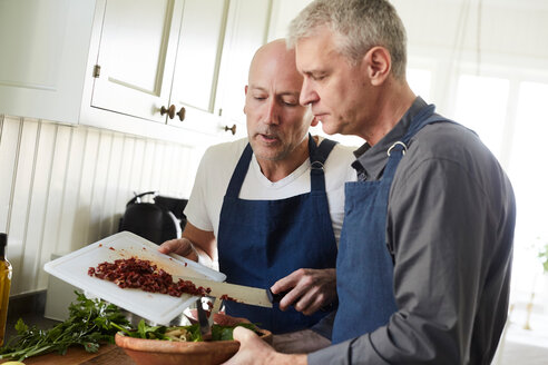 Bald mature man assisting friend in cooking food at home - MASF11841
