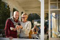 Cheerful mature woman showing mobile phone to bald man with friends in background on porch - MASF11853