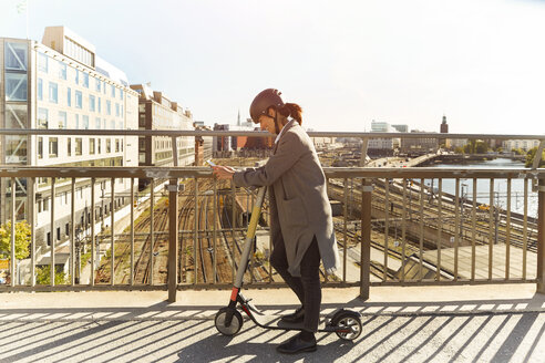 Full length side view of mature woman using smart phone while standing with electric push scooter on bridge in city - MASF11862
