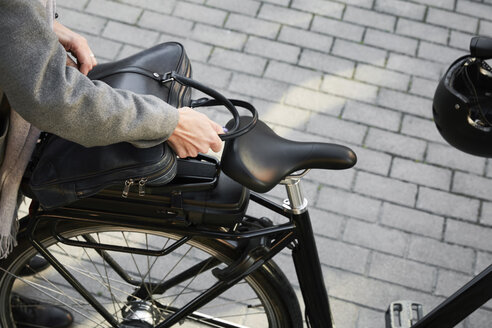 Cropped image of woman positioning bag on electric bicycle in city - MASF11868