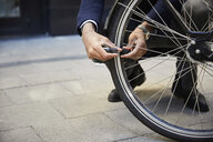 Low section of male commuter locking electric bicycle wheel against building in city - MASF11877