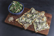 Tarte Flambee with camembert and thyme creme fraiche and red onion on chopping board, lamb's lettuce with pear in bowl - STBF00259