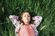 Portrait of girl relaxing on a meadow with daisy in her mouth - ANHF00101