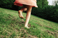 Back view of girl running barefoot on a meadow, partial view - ANHF00104