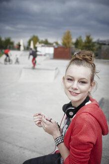 Portrait of smiling teenage girl at a skatepark - RORF01833