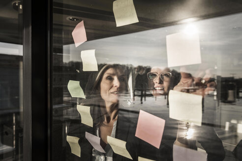 Two businesswomen brainstorming, putting sticky notes on window pane - MJRF00083
