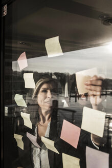 Two businesswomen brainstorming, putting sticky notes on window pane - MJRF00089