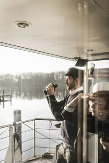 Colleagues working on a houseboat, watching surroundings with binoculars - MJRF00101
