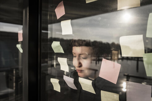 Tired woman leaning against window pane with sticky notes - MJRF00107