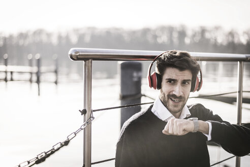 Businessman on a houseboat using smartwatch, making a call, wearing headphones - MJRF00116