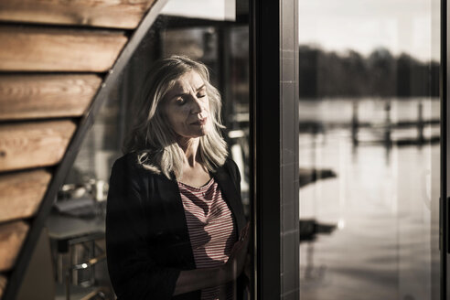 Businesswoman standing on a houseboat,enjoying the sun at the window with eyes closed - MJRF00119
