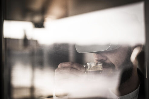 Businessman with VR glasses enjoying his coffee - MJRF00131