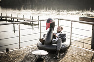 Hip businessman working on a houseboat, sitting a floating swan, using digital tablet - MJRF00134
