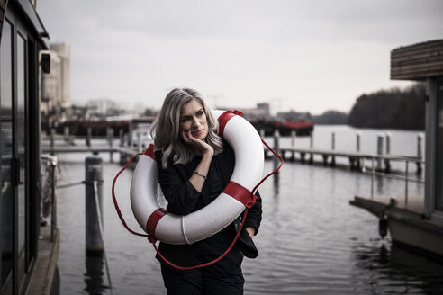 Businesswoman standing on a houseboat, looking worried, with lifesaver around - MJRF00143