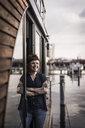 Woman leaning in window of a houseboat, taking a break - MJRF00146