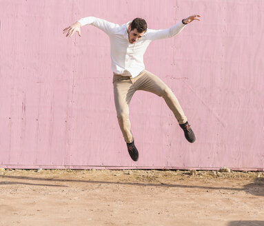 Exuberant young man jumping in front of pink wall - UUF16749