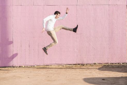 Exuberant young man jumping in front of pink wall - UUF16752