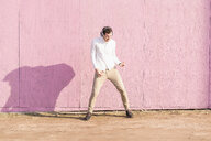 Exuberant young man listening to music in front of pink wall - UUF16755