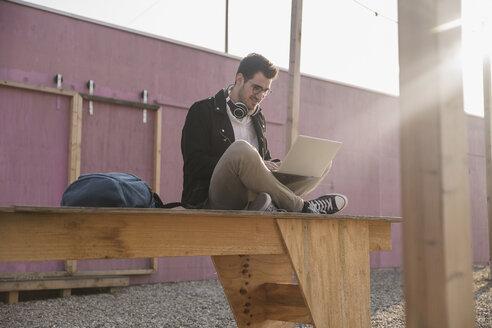 Young man sitting on platform using laptop - UUF16764