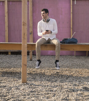 Young man sitting on platform holding cell phone - UUF16767