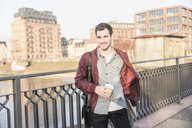 Smiling young man with tablet, bag and takeaway coffee on a bridge in the city - UUF16794