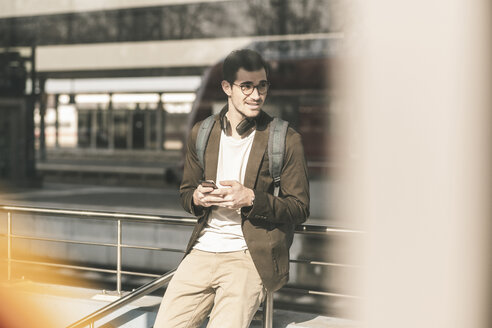 Smiling young man with cell phone at the station - UUF16815